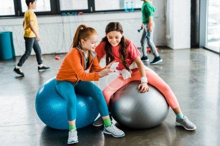 Niños usando smartphone mientras están sentados en pelotas de fitness