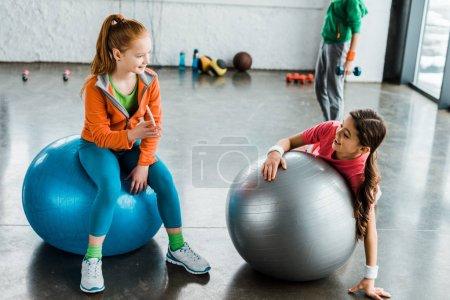 Photo pour Enfants avec smartphone utilisant des balles de fitness dans la salle de gym - image libre de droit
