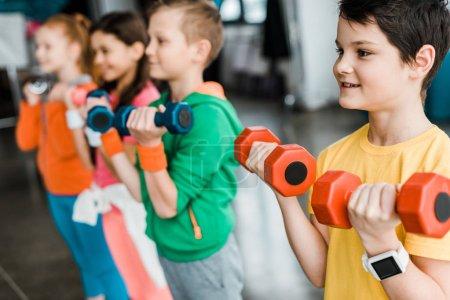 Photo pour Enfants mignons de formation avec des haltères colorés - image libre de droit