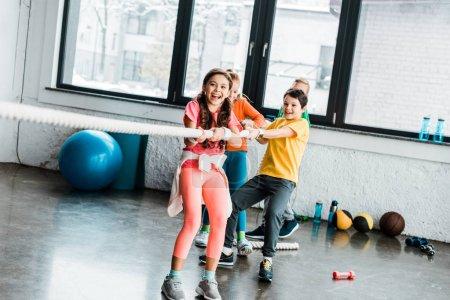 Photo pour Excité les gosses jouant acharnée dans la salle de gym - image libre de droit