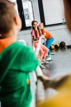 Photo pour Enfants enthousiastes jouant remorqueur de guerre dans la salle de gym - image libre de droit