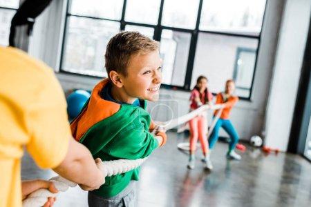 Photo pour Riant enfants jouant remorqueur de guerre ensemble - image libre de droit