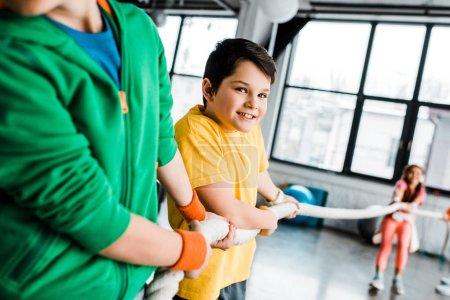 Photo pour Enfants préados tire sur la corde dans la salle de gym avec sourire - image libre de droit