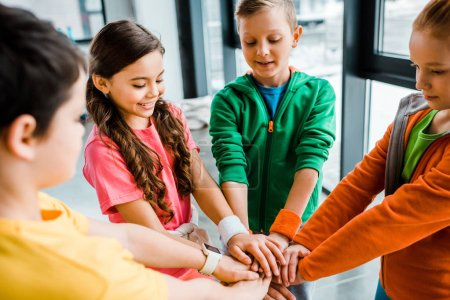 Photo for Group of kids preparing for sport competition and holding hands - Royalty Free Image