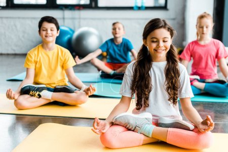 Photo for Pleased preteen kids stretching on fitness mats - Royalty Free Image