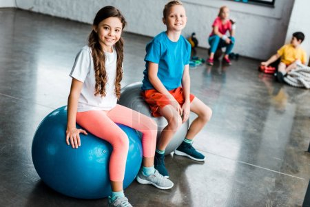Preteen kids sitting on fitness balls and looking at camera