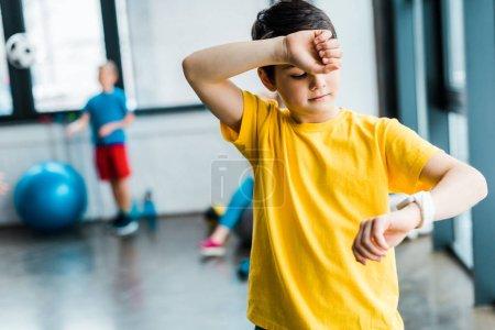 Photo pour Fatigué de garçon regardant smartwatch dans la salle de gym - image libre de droit