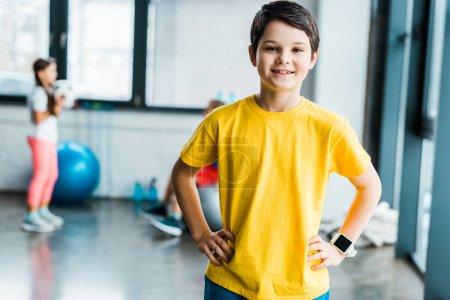 Photo pour Souriant brunette garçon posant avec les bras akimbo dans la salle de gym - image libre de droit