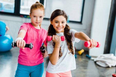 Photo pour Enfants actifs, faire des exercices avec des haltères dans la salle de gym - image libre de droit