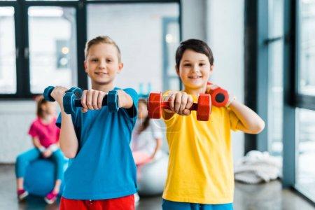 Garçons excités faisant de l'exercice avec haltères ensemble