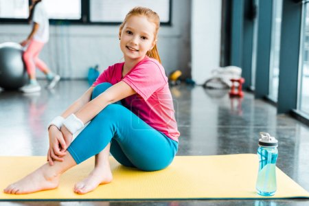 Photo for Barefooted kid sitting on yellow fitness mat with smile - Royalty Free Image