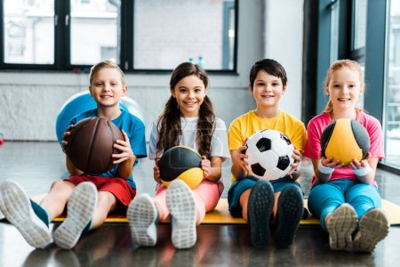 Preteen kids sitting on fitness mat with balls