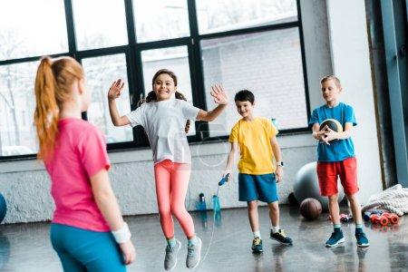 Photo pour Inspiré des enfants sautant avec corde dans une salle de sport à sauter - image libre de droit