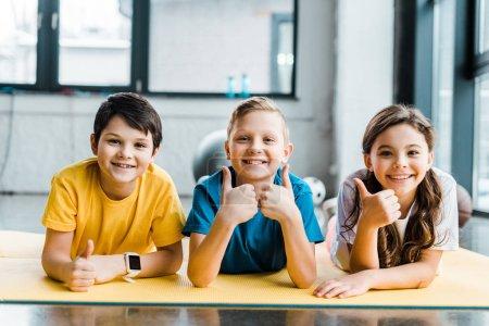 Foto de Riendo a los niños posando en la alfombra de fitness con los pulgares para arriba - Imagen libre de derechos