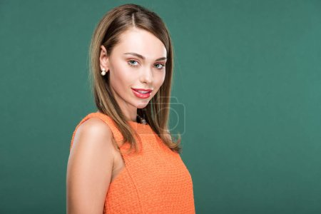Photo for Beautiful fashionable woman in orange looking at camera isolated on green with copy space - Royalty Free Image