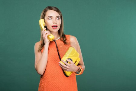 Photo for Beautiful stylish woman talking on retro telephone isolated on green with copy space - Royalty Free Image