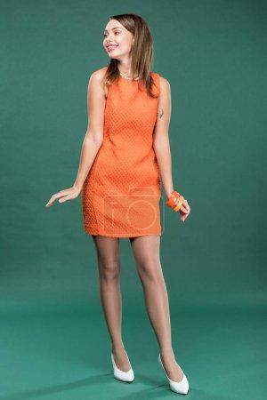 Photo for Beautiful stylish woman in orange dress posing on green background - Royalty Free Image