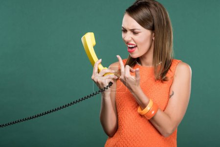 Photo for Beautiful angry woman yelling at retro telephone and showing middle finger isolated on green - Royalty Free Image