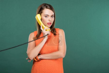 Photo for Beautiful stylish woman looking at camera and talking on retro telephone isolated on green with copy space - Royalty Free Image