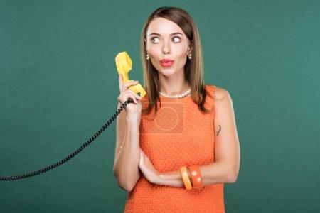 Photo pour Belle femme élégante moue des lèvres et la tenue rétro téléphone isolé sur vert - image libre de droit