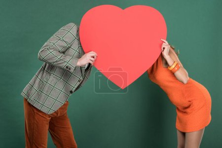 Photo for Man and woman covering faces with heart shaped paper card isolated on green - Royalty Free Image