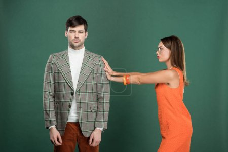 Photo pour Belle femme poussant bel homme en vêtements vintage isolé sur vert - image libre de droit