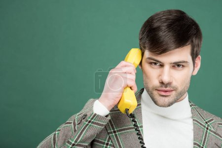 Photo for Handsome man in vintage clothes talking on retro telephone and looking at camera isolated on green - Royalty Free Image