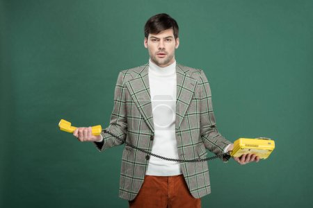 Photo pour Confondu le bel homme en vêtements vintage tenir téléphone cadran rotatif et regardant la caméra isolée sur vert - image libre de droit