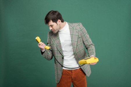 Photo pour Insatisfait de bel homme en vêtements vintage regardant rétro téléphone isolé sur vert - image libre de droit