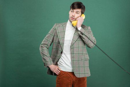Photo for Confused handsome man in vintage clothes talking on retro telephone isolated on green - Royalty Free Image