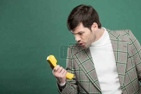 Photo for Handsome man in vintage clothes shouting at retro telephone isolated on green with copy space - Royalty Free Image