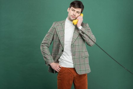 Photo for Handsome man in vintage clothes talking on retro telephone isolated on green - Royalty Free Image