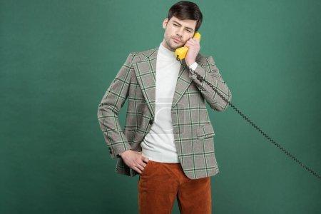 Photo pour Bel homme en vêtements vintage parlant sur téléphone rétro isolé sur vert - image libre de droit