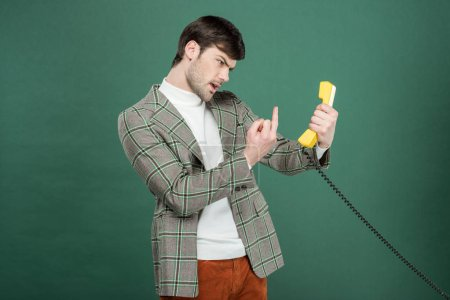 Photo for Angry handsome man in vintage clothes showing middle finger in front of retro telephone isolated on green - Royalty Free Image