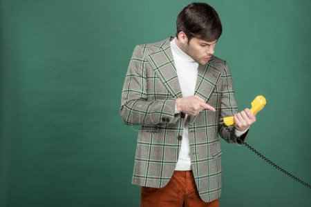 Photo for Dissatisfied handsome man in vintage clothes pointing with finger at retro telephone isolated on green - Royalty Free Image