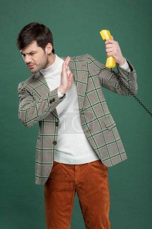 Photo pour Insatisfait de bel homme en vêtements vintage refusant l'appel téléphonique et gesticulant avec main isolé sur vert - image libre de droit
