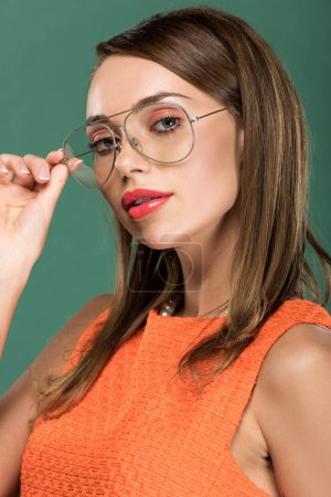 Photo for Beautiful stylish woman in orange and glasses looking at camera and posing isolated on green - Royalty Free Image