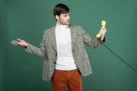 Photo for Surprised handsome man in vintage clothes looking at retro telephone and gesturing with hand isolated on green - Royalty Free Image