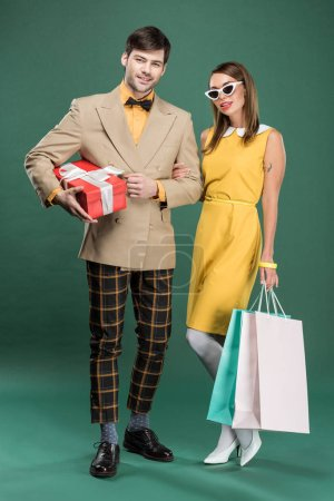 Photo for Beautiful couple in vintage clothes with shopping bags and gift box on green background - Royalty Free Image