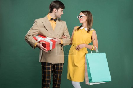 Photo for Beautiful couple in vintage clothes with shopping bags isolated on green - Royalty Free Image