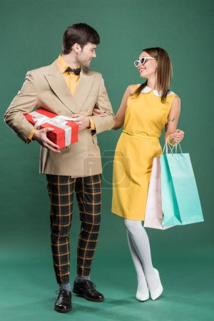 Photo for Beautiful smiling couple in vintage clothes with shopping bags and gift box on green background - Royalty Free Image