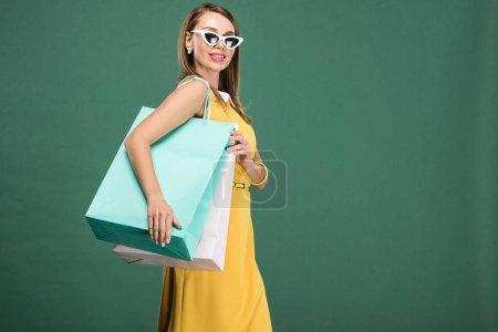 Photo pour Femme élégante en robe jaune et les lunettes de soleil de sacs isolés sur vert - image libre de droit