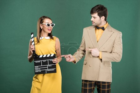 Photo for Man in vintage clothes pointing with fingers at woman with clapperboard isolated on green - Royalty Free Image