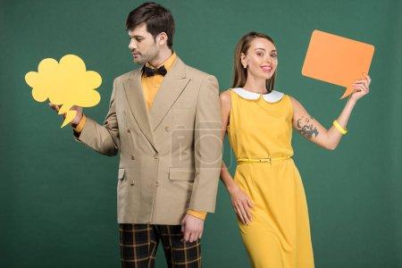 Foto de Atractiva pareja en ropa vintage con discurso burbuja y burbuja de pensamiento aislado en verde - Imagen libre de derechos