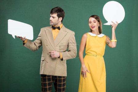 Foto de Hermosa pareja de ropa vintage con discurso burbuja y burbuja de pensamiento aislado en verde - Imagen libre de derechos