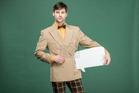 Photo for Handsome man in vintage clothes holding speech bubble and looking at camera isolated on green - Royalty Free Image