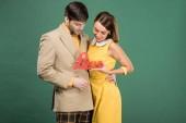 """Постер, картина, фотообои """"красивая пара в винтажной одежды, холдинг декоративные слово «любовь» изолированные на зеленый"""""""