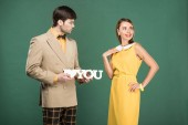 man presenting decorative 'i love you' sign to beautiful woman in vintage clothes isolated on green