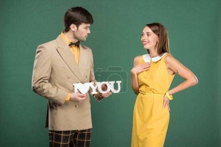 """Photo pour Homme présentant décoratif """"je t'aime"""" signe à belle femme surprise en vêtements vintage isolé sur vert - image libre de droit"""