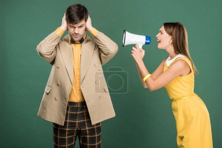 Photo for Man in vintage clothes covering ears with hands while angry woman yelling in loudspeaker isolated on green - Royalty Free Image